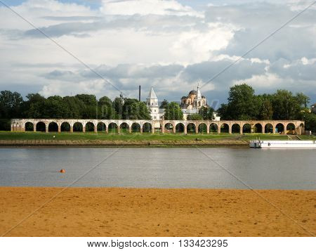 Beach Volkhov river ancient shopping arcade two churches trees and sky.