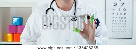 Friendly pedriatrician at his office with toys