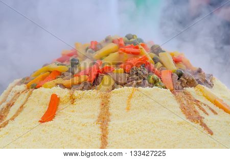 Preparation of a large couscous outdoors. Moroccan street festival