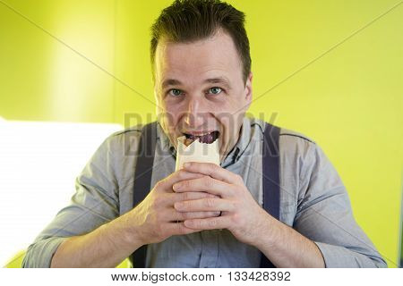 Man eats a sandwich in cafeteria.  Fastfood