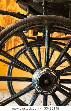 Close up view of carriage wheels with long spokes and a vine design painted on its rim parked in front of yellow wall