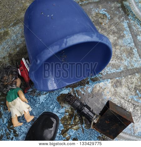 Abandoned toys next to a rubber boot and water pump overhead cropped shot concept of natural disaster