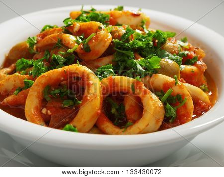 Calamari stewed in tomato and onion sauces with olives topped with parsley. Horizontal shot