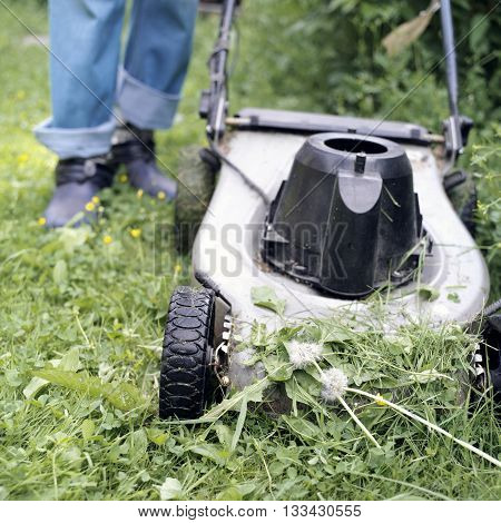 Electric lawn mower in the foreground and human legs in the blurred background selective focus outdoor shot