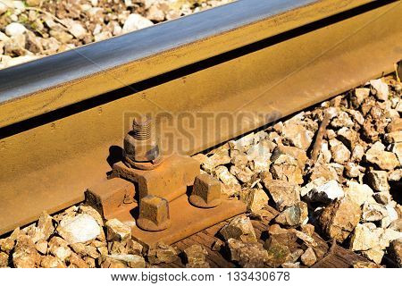 Close up detail of a rail track showing the steel track mounted on wooden sleepers in gravel with rusty bolts in a travel and transport concept
