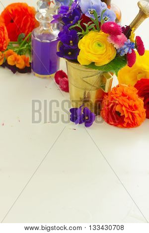 Fresh flowers, mortar and bottles of potions, herbal medicine concept, copy space on white table