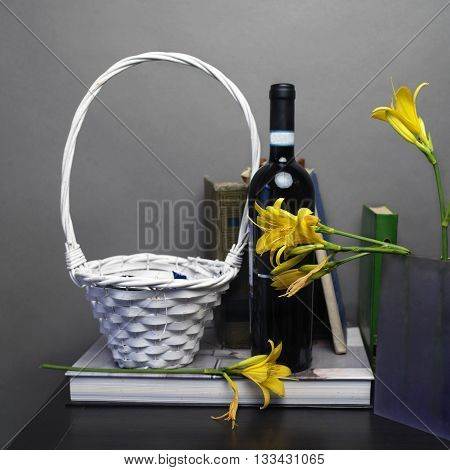 Wicker basket and a bottle of red wine next to the vase with beautiful yellow day lily front studio shot