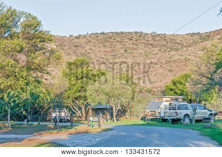 MOUNTAIN ZEBRA NATIONAL PARK SOUTH AFRICA - FEBRUARY 18 2016: A tent caravan and vehicles at the camping grounds in the Mountain Zebra National Park near Cradock at sunset