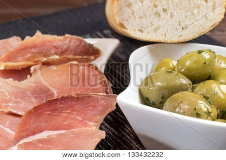 Refreshments of sliced Spanish ham green olives and bread is lying on a wooden table and in a white bowl. Horizontally.