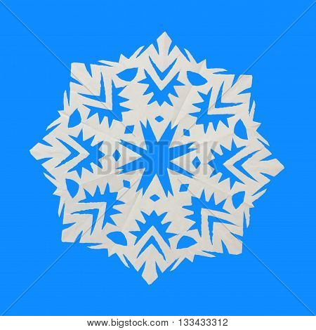 White snowflake cut out of paper lies on blue background