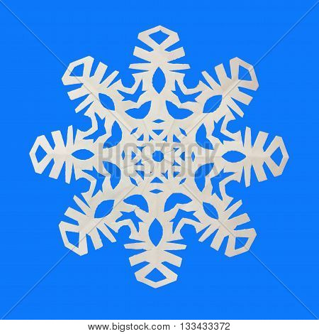 White snowflake cut out of paper lies on a blue background