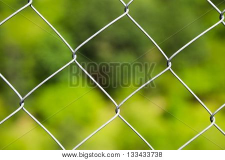 Detail of a diamond mesh wire fence with selective focus to the steel wire over a blurred green background