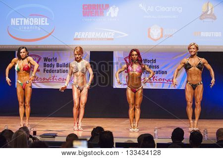 MAASTRICHT THE NETHERLANDS - OCTOBER 25 2015: Female fitness models Gerbel Mikk Sonja den Breems-Tanamal and two other competitors flex their muscles and show their best physique in a front pose on stage at the World Grandprix Bodybuilding and Fitness
