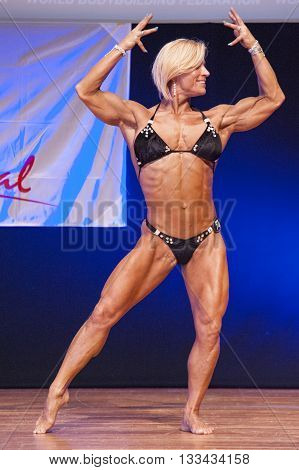 MAASTRICHT THE NETHERLANDS - OCTOBER 25 2015: Female fitness model Gerbel Mikk flexes her muscles and shows her best physique in a front double biceps pose on stage at the World Grandprix Bodybuilding and Fitness of the WBBF-WFF