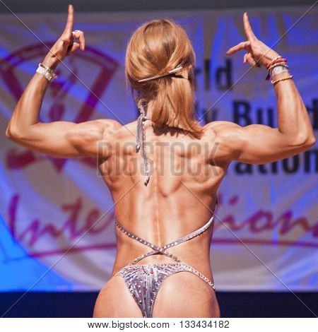 MAASTRICHT THE NETHERLANDS - OCTOBER 25 2015: Female fitness model flexes her muscles and shows her best physique in a back doiuble biceps pose on stage at the World Grandprix Bodybuilding and Fitness of the WBBF-WFF