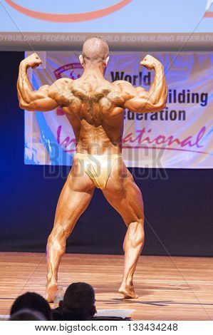 MAASTRICHT THE NETHERLANDS - OCTOBER 25 2015: Male bodybuilder flexes his muscles and shows his best physique in a back double biceps pose on stage at the World Grandprix Bodybuilding and Fitness of the WBBF-WFF