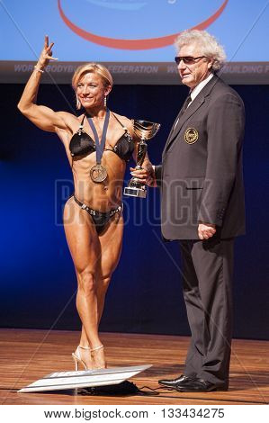MAASTRICHT THE NETHERLANDS - OCTOBER 25 2015: Female bodybuilder Gerbel Mikk celebrates her victory on stage with the official at the World Grandprix Bodybuilding and Fitness of the WBBF-WFF
