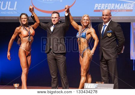 MAASTRICHT THE NETHERLANDS - OCTOBER 25 2015: Female bodybuilders celebrate their victory on stage with officials at the World Grandprix Bodybuilding and Fitness of the WBBF-WFF