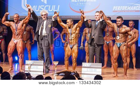 MAASTRICHT THE NETHERLANDS - OCTOBER 25 2015: Male bodybuilders celebrate their victory on stage with the officials and the national flag of Iran at the World Grandprix Bodybuilding and Fitness of the WBBF-WFF