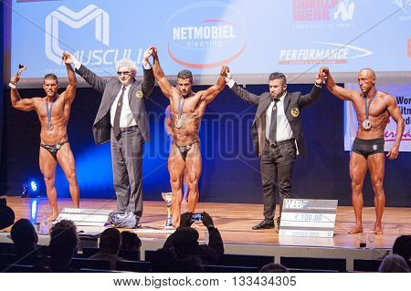 MAASTRICHT THE NETHERLANDS - OCTOBER 25 2015: Male bodybuilders celebrate their victory on stage with officials at the World Grandprix Bodybuilding and Fitness of the WBBF-WFF on October 25 2015 at the MECC Theatre