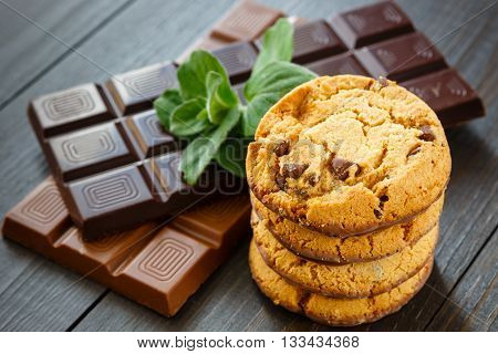 Chocolate cookies stacked vertical with milk and dark chocolate bar