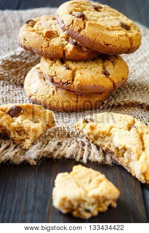 Chocolate whole cookies and pieces with crumbs on burlap on rustic wood table