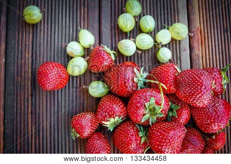 Fresh strawberries and gooseberries on old texture background