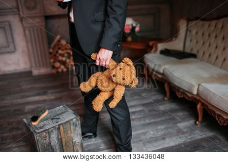 Handsome elegant young fashion man in black classical costume suit, white shirt, holding a gift of little teady bear