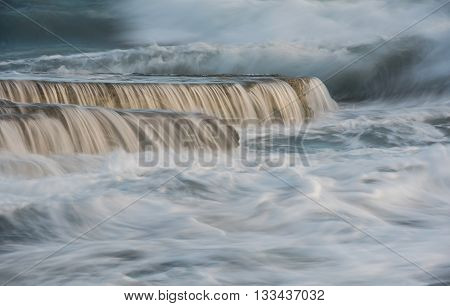 Powerful sea waves crashing on sea rock plates creating small waterfalls