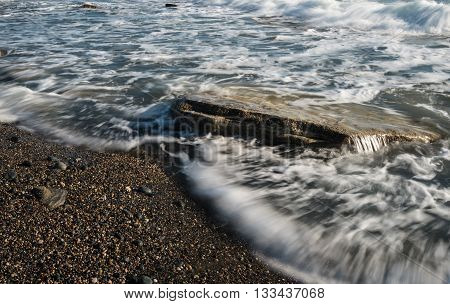 Sea waves flowing above a sea rock creating a beautiful nature water background. Long exposure photo.