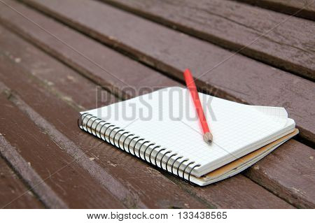 sketchbook and a pencil lying on a wooden bench