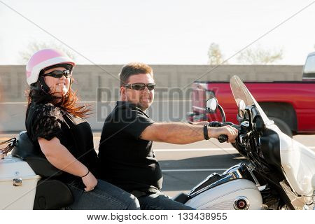 A father and his daughter ride on a motorcycle on the freeway. She has a pink helmet but he has no helmet.