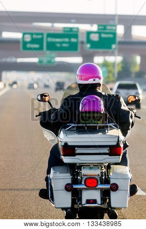 View from the back of a father and daughter riding a motorcycle on a freeway. Main subject of the image is the father's face in the rearview mirror.