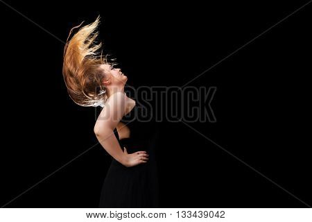 A teenage girl with beautiful long blond hair flips her hair against a black background. Her hair is backlit.