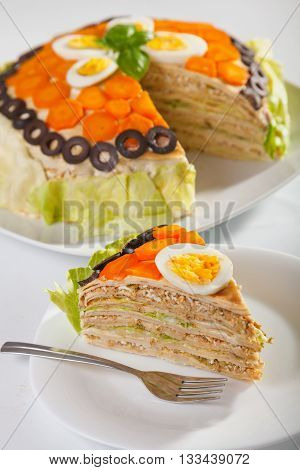 Salty cake made from pancakes tuna fish eggs carrots olives and iceberg salad. Vertical shot