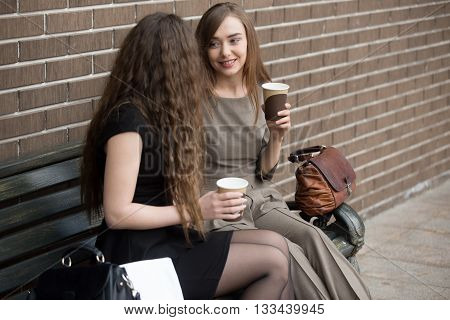 Two Young Beautiful Women Holding Paper Cups Of Coffee And Chatting On Bench