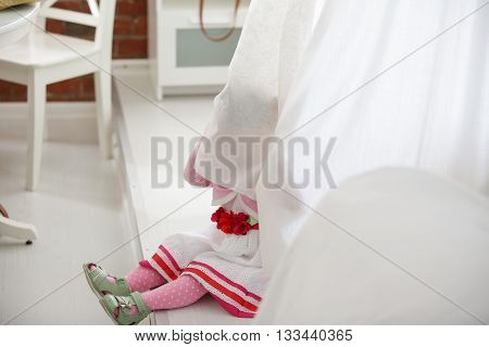 Portrait of little girl peeking from curtains at home. White dress