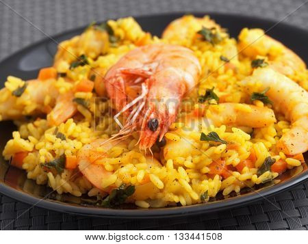 Seafood risotto with shrimps curry and herbs. Horizontal shot macro