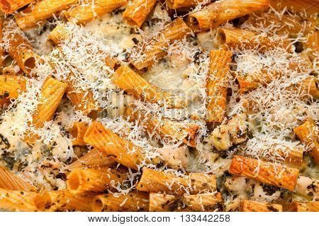 Baked Penne pasta with parmesan cheese. Shot from above. Close up horizontal shot