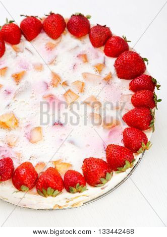 Cake with strawberries gelly yogurt and cherries shot from above. Cropped view. Isolated on white background