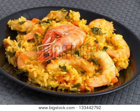 Seafood risotto with shrimps curry and herbs. Horizontal shot tilted