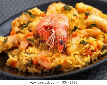 Seafood risotto with shrimps curry and herbs. Close up.