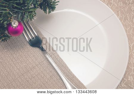 plate and fork on linen tablecloths in a floral pattern and linen napkin on a table with a Christmas tree decorated with Christmas decoration ball