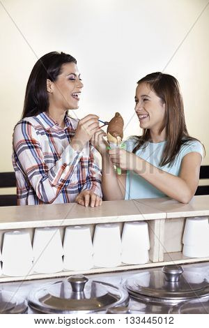 Mother And Girl Having Chocolate Ice Cream At Counter