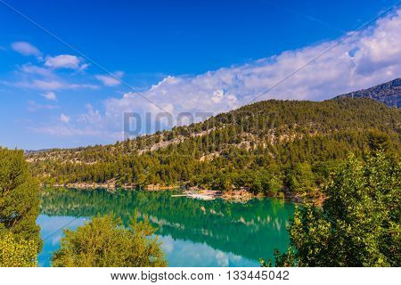 Smooth emerald river water reflects the sky and wooded shore. Mountain canyon Verdon in the French Alps