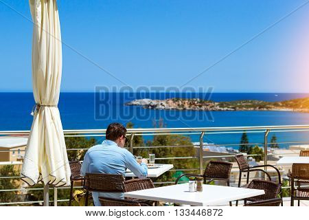 Young man in blue shirt is having lunch on veranda of restaurant, overlooking the Cretan sea. Bali, Rethymno, Crete, Greece