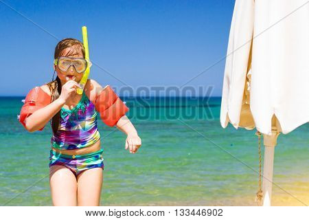 Cute happy girl child relaxing on the shores of Cretan sea in swimming glasses with breathing tube and in rescue arm cover. Sunny sandy Livadi beach in sea Bay of resort village Bali Rethymno Crete Greece