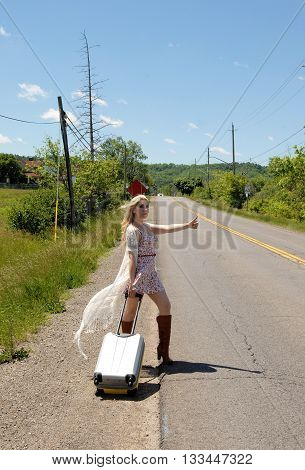 A lovely blond woman standing on a country road waiting for a car for a rait in a dress and a suitcase with her thump's up.