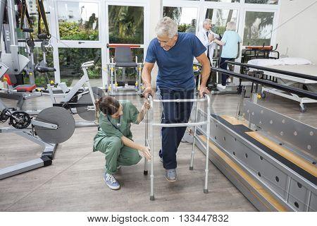 Female Nurse Assisting Senior Man With Walker In Fitness Studio