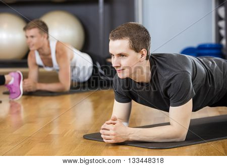 Man Performing Plank Position In Gym